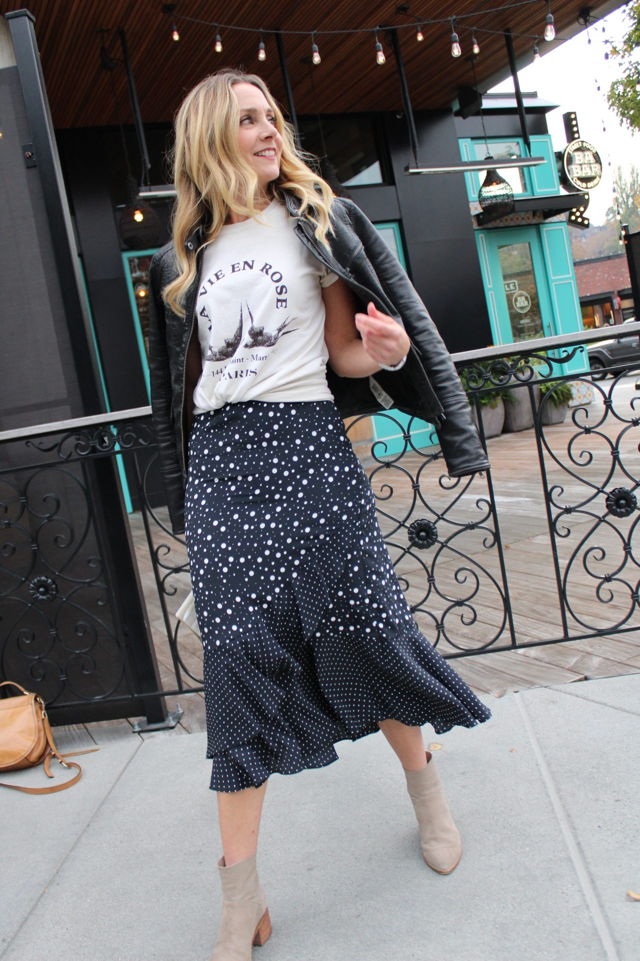 leather jacket and french graphic tee with ruffled wrap polka dot midi skirt