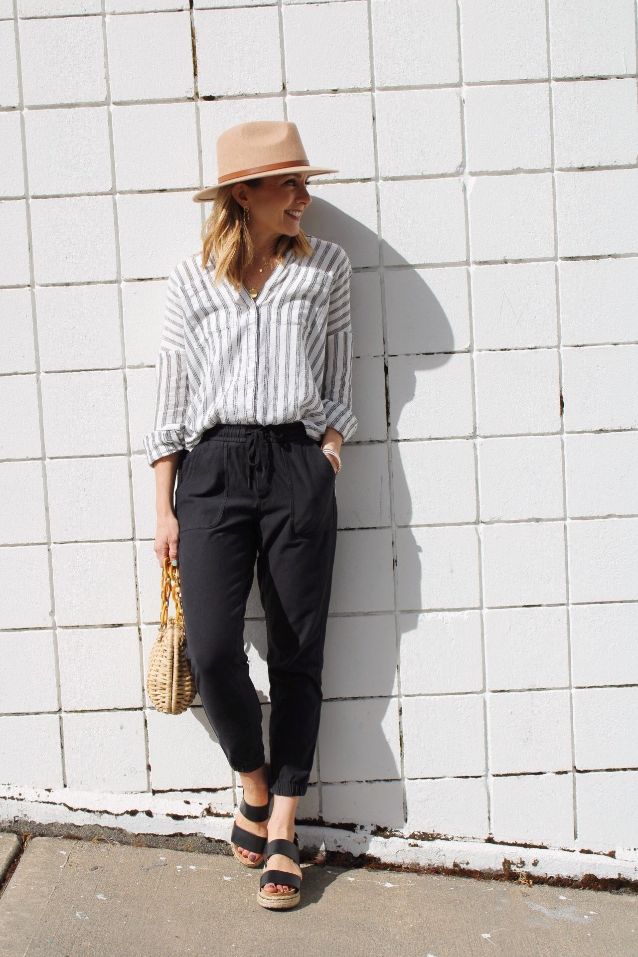 striped linen button down shirt with black joggers, black sandals, and beige felt fedora hat