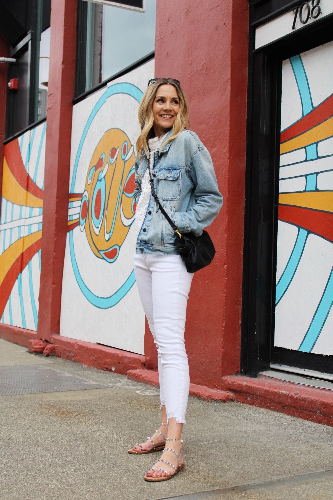 white monochrome outfit with white denim, white eyelet top, denim jacket, studded sandals and black crossbody bag