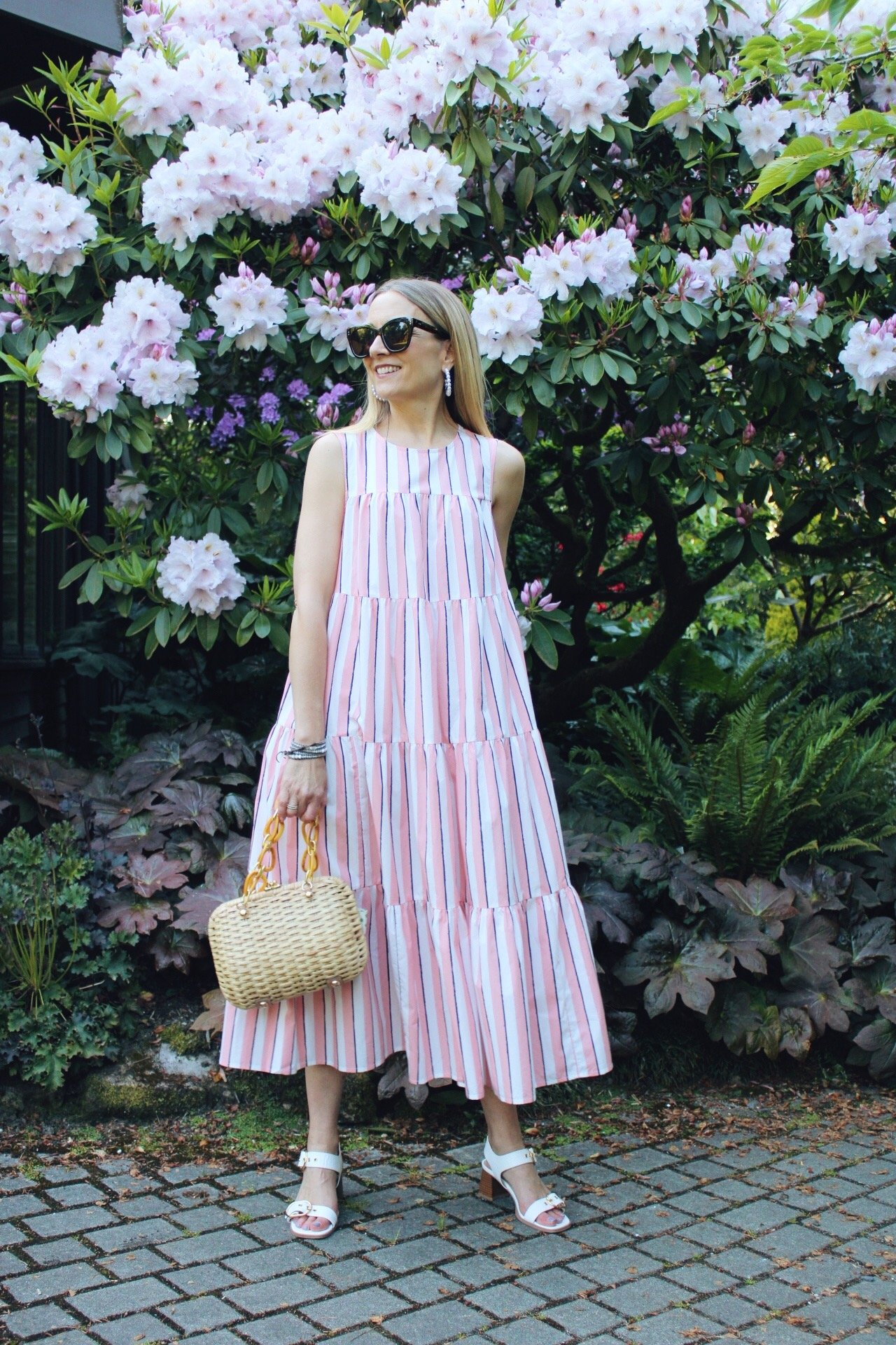 pink striped sundress with wicker basket bag and white heels