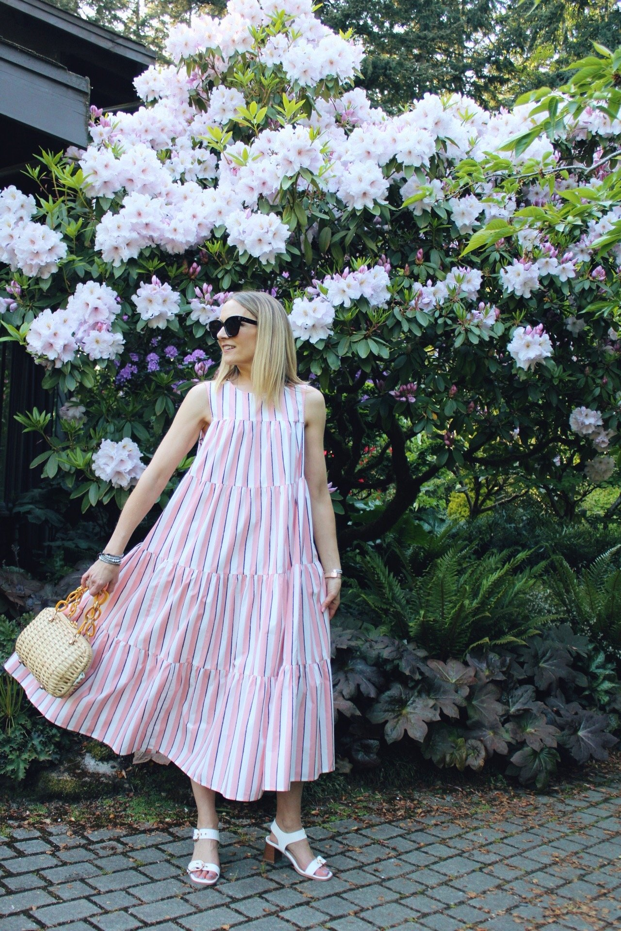 pink midi tiered ruffle sundress with white sandals and wicker bag
