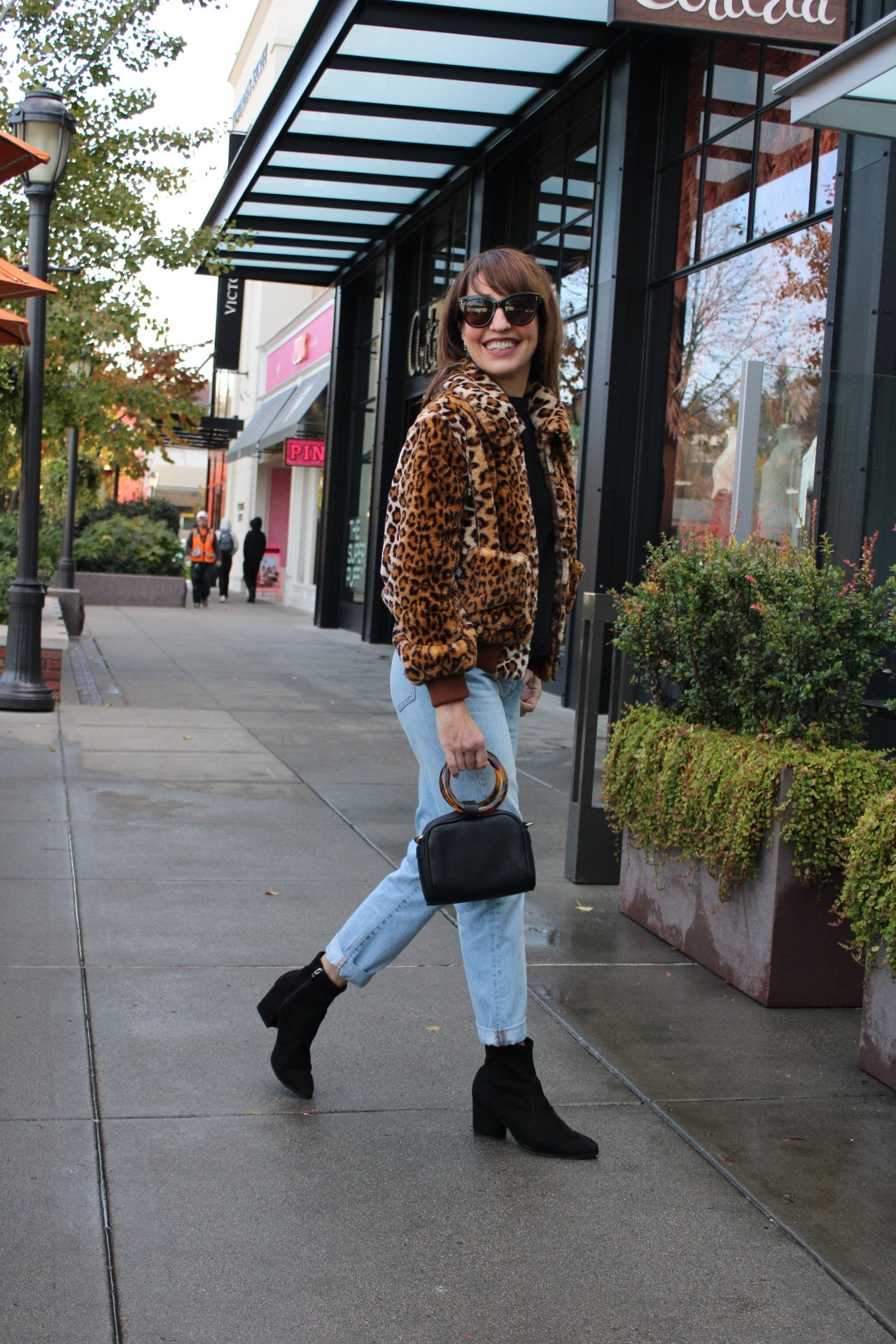 faux fur leopard coat with lightwash jeans and black booties