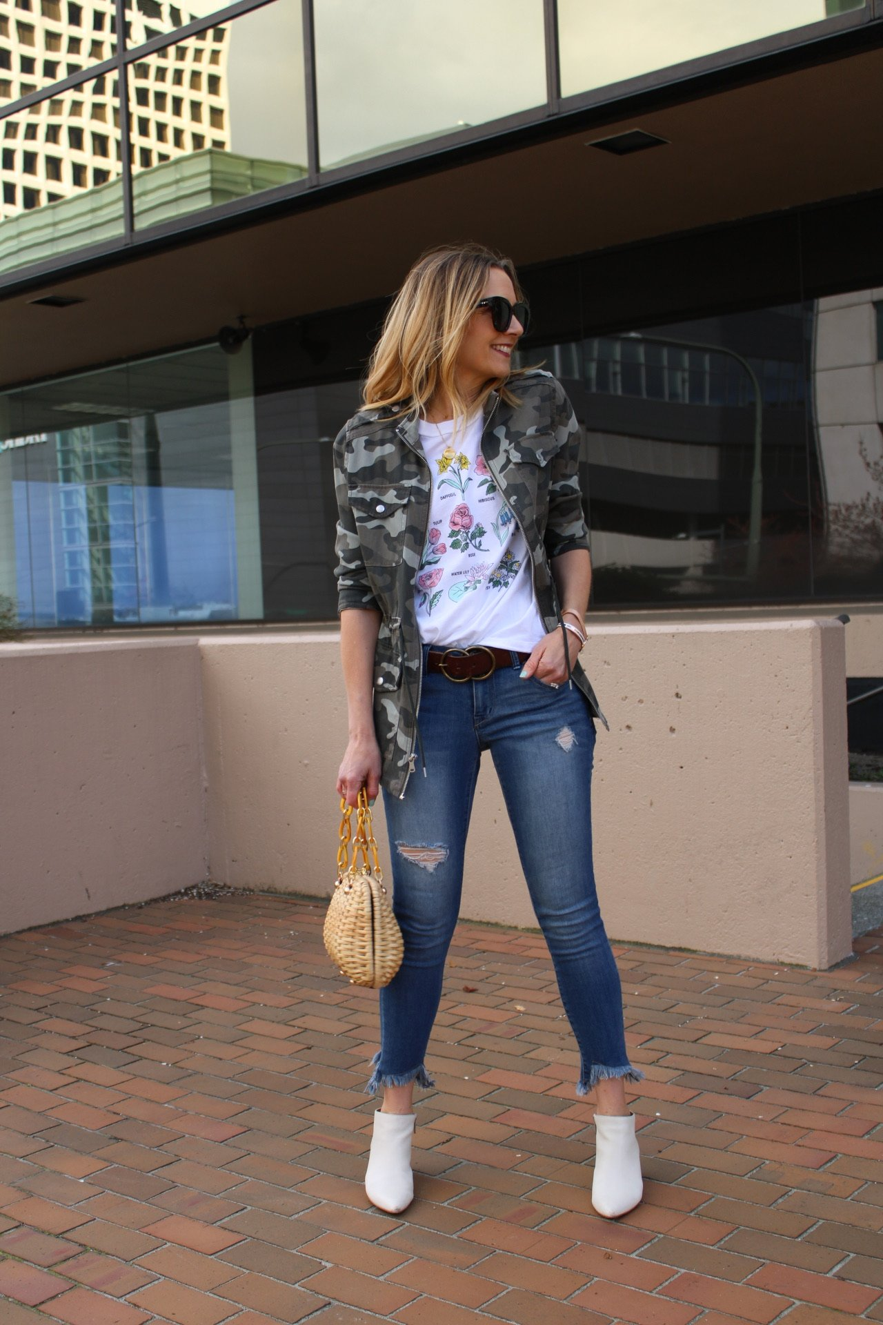 lightweight camo jacket with floral graphic tee and white booties