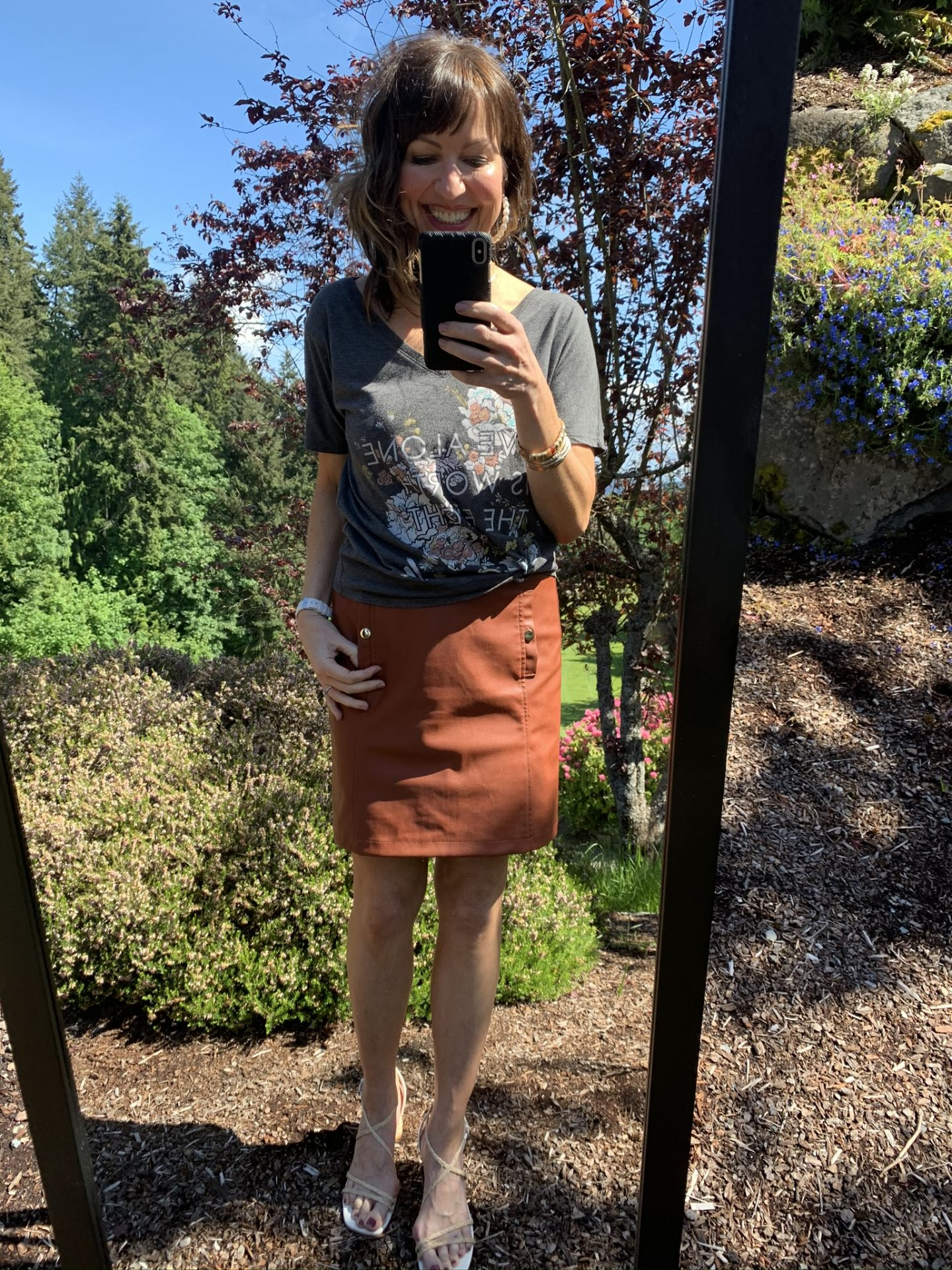 mirror selfie with switchfoot band graphic tee and rust faux leather miniskirt and heels