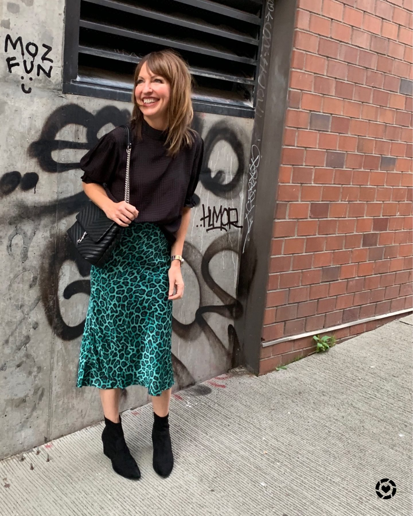 green leopard midi skirt with black top and black booties