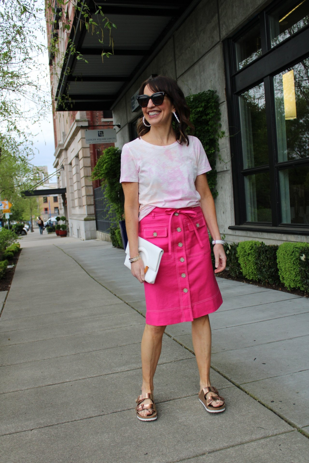jcrew tie dye tee with pink button front knee length skirt and rose gold birkenstock sandals