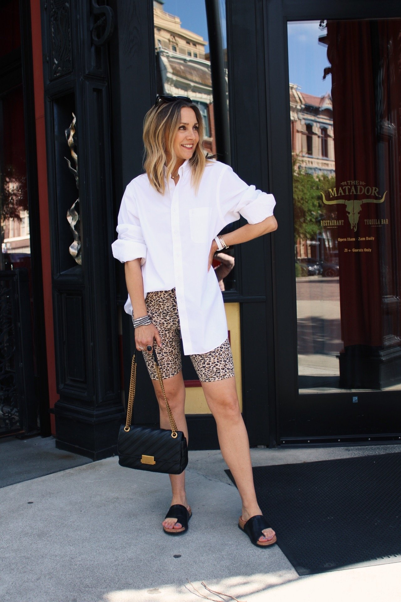 white oversized button down top with leopard print biker shorts summer outfit