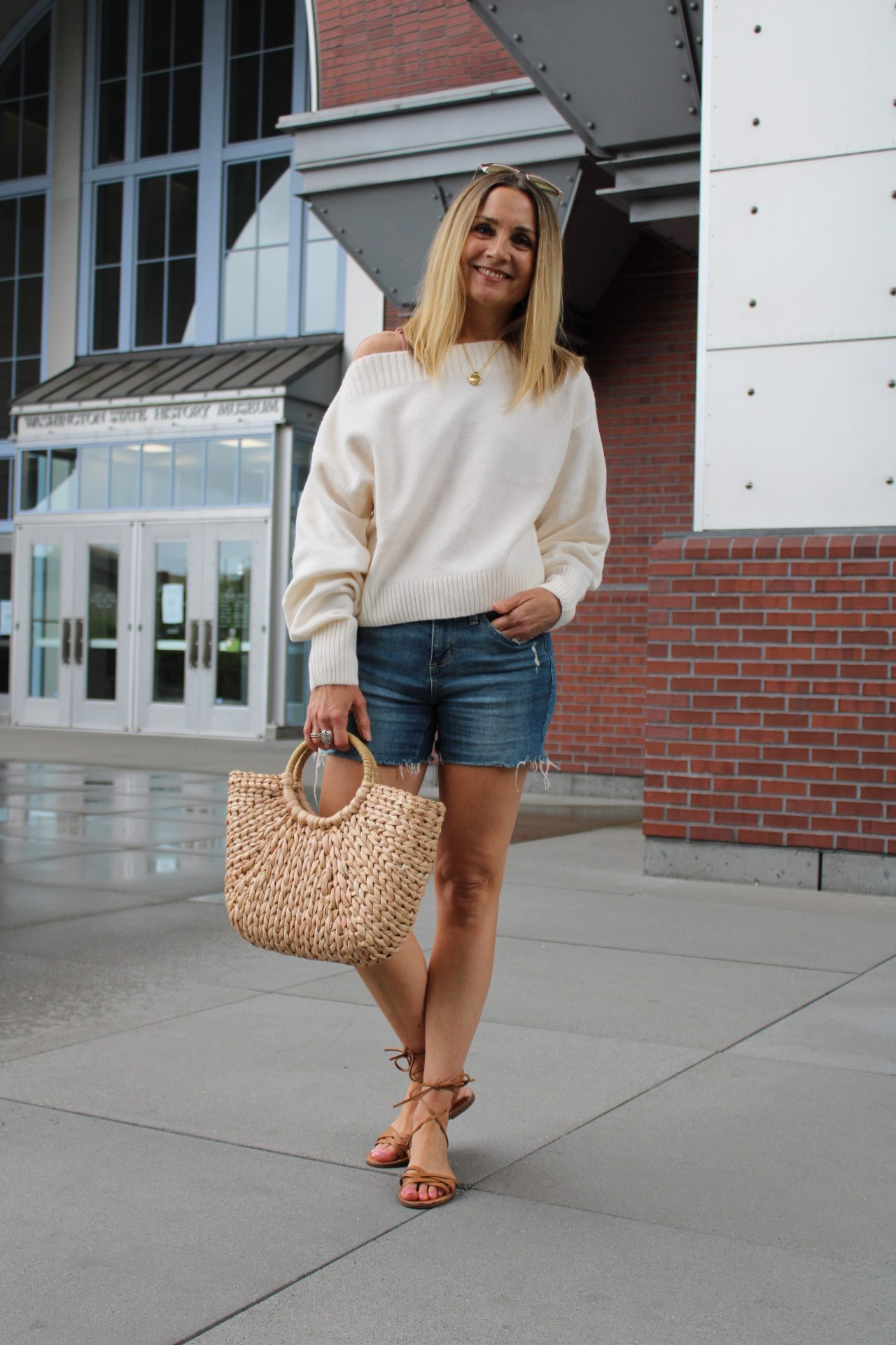 boatneck off white sweater with denim shorts and straw bag summer outfit